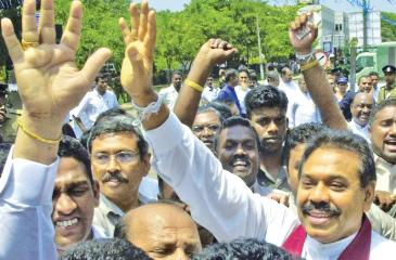 COLOMBO, SRI LANKA: Sri Lankan Prime Minister Mahinda Rajapakse (R) waves to crowds 07 October 2005 in Colombo shortly after filing his nomination papers to contest the 17 November 2005 presidential elections. Thirteen candidates entered the fray, but the contest is seen largely as a battle between Rajapakse and his main challenger, opposition leader Ranil Wickremesinghe. AFP PHOTO/Lakruwan Wanniarachchi