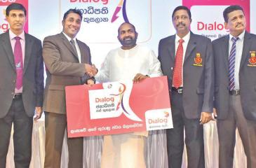 Harsha Samaranayake the Senior General Manager - Brand and Media of Dialog, presents the sponsorship cheque to Ranjith Siyambalapitiya MP and president of the Sri Lanka Volleyball Federation as AS Nalaka, General Secretary of the Sri Lanka Volleyball Federation looks on