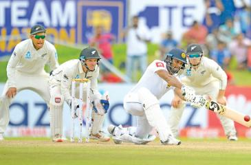Dimuth Karunaratne sweeps a ball during his unbeaten innings of 71 on the fourth day of the first cricket Test against New Zealand in Galle