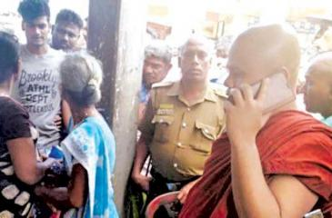 The Tamil woman is seen here surrounded by an angry mob led by a Buddhist monk