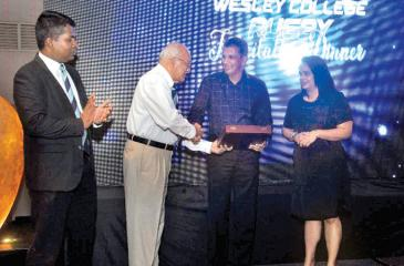 Roshan Mahanama flanked by his wife Jeeva is presented with a memento from former Wesley College principal MAP Fernando