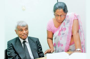 Kanthi Swarnalatha reads out a document aloud to Udayasiri Rajapaksa.             Pic : Roshan Pitipana