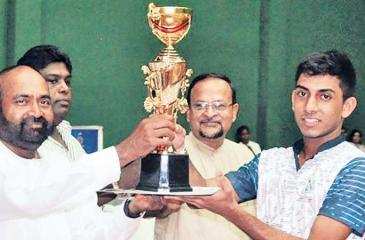Richmond skipper Chamath Dias receiving the Super 'A' division champion's trophy from Sabaragamauwa Province Badminton Association president Ranjith Siyambalapitiya