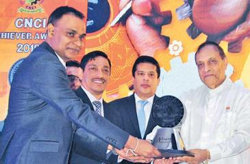 A Royal Ceramics official receives one of the awards from Speaker Karu Jayasuriya.