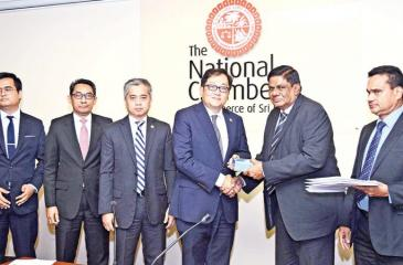 Malaysian High Commissioner, Tan Yang Thai receives the souvenir from President, National Chamber, Asela de Livera.  Deputy President, National Chamber, Deepal Nelson and officials look on.