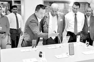 Huawei Device Sri Lanka Country Manager Peter Liu shows the latest Huawei Smartphones to Singer Sri Lanka Group Chairman Mohan Pandithage. Huawei Device Sri Lanka General Manager Kalpa Perera, Singer Sri Lanka Group CEO Mahesh Wijewardene and Singer Sri Lanka PLC Marketing Director Kumar Samarasinghe look on.