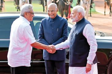 President Rajapaksa (L) shakes hands with India's Prime Minister Modi (R) as India's President Ram Nath Kovind looks on during a ceremonial reception