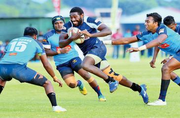 Police Centre Emoci Vunivosa makes a break hotly pursued by two Air Force defenders in their Dialog 'A' Division League Rugby match played at Ratmalana yesterday which Police won 36 – 15. Picture by Saman Sri Wedage