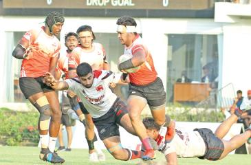 CH and FC scrum half Avishka Lee faces opposition from Kandy SC centre Tarinda Ratwatte as his team mate Samuel Maduwantha joins in for  support (Pic by Shan Rambukwella)