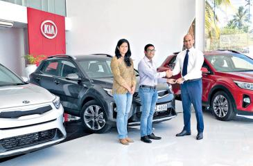 Kia Motors (Lanka) Executive Director /Chief Operating Officer  Andrew Perera (extreme right) presents the keys to the first customer for the Kia Stonic at the company's Malabe complex.