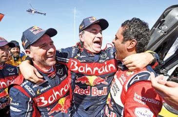 First-placed for the auto category JCW X-RAID Team Spain's driver Carlos Sainz (C), celebrates as he is congratulated by second-placed Toyota's team Qatar's driver Nasser Al-Attiyah (R) and by third-placed JCW X-RAID Team France's Stephane Peterhansel on the finish area in Qiddiya at the end of the stage 12 of the Dakar 2020 between Haradh and Qiddiya, Saudi Arabia, on January 17, 2020. (Photo by FRANCK FIFE / AFP)
