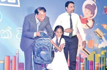 Group Chairman, Richard Pieris and Company, Dr. Sena Yaddehige presents a bag containing school books to a student. Manager, Group Human Resource Operations and Industrial Relations, Richard Pieris and Company, Sydney Gunawardana looks on.