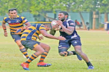Police's Fijian centre Emosi Vunivosa is stopped in his tracks by the Army defence in their league rugby match at Police Park yesterday (Pic Shan Rambukwella)