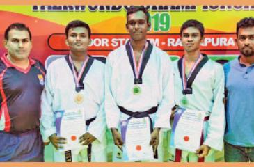 Akila Upamal (third from left) his coach Priyantha Kumara (left) and master in charge Priyadharshana Cooray (right) pose for a picture at the Sri Lanka Schools Taekwondo Championship held in Ratnapura