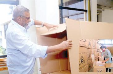 Counting  of ballot papers will not take place the same day this time, due to  the health guidelines of the Covid-19 pandemic. Here the Election Commission Chairman Mahinda Deshapriya shows the Sunday Observer  photojournalist where the ballot boxes will be sealed until they are  opened for counting on August 6. Right: A woman member of the poll staff at the  D.S. Senanayake College making the final preparations. Including health officials, almost 400,000 staff will be deployed  on election duty this year.