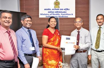Want Want Group donated Slightly Acidic Hypochlorous Acid Water generators, which dispense a chlorine-based solution proven to be an effective disinfectant against the Covid-19 virus, to the Health Ministry recently. Here National Olympic Committee Secretary General Maxwell de Silva, who coordinated with Want Want Group, presents the donation to Health Minister Pavithra Wanniarachchi.
