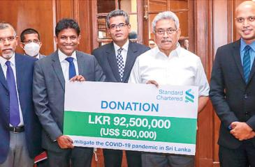 President Gotabaya Rajapaksa symbolically accepting the donation from Bingumal Thewarathanthri, CEO, Standard Chartered Sri Lanka (3rd left), in the presence of Dr. Mahesh Gunasekara, Director General, Sri Lanka Red Cross Society (left), Major General Suresh Sallay, Director of State Intelligence Service (second left), Major General Dr.SanjeewaMunasinghe, Secretary to the Ministry of Health (third right) and Anuk De Silva, Head of Corporate Affairs, Brand & Marketing, Standard Chartered Sri Lanka (right).