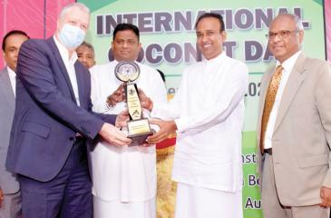 State Minister of Plantations, Arundhika Fernando and Minister of Plantations, Dr. Ramesh Pathirana present the award to Nestlé's Managing Director Fabrice Cavallin. Chairman of the Coconut Development Authority, the Coconut Cultivation Board and the Coconut Research Institute, Jayantha Wickramasinghe looks on.