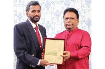 National athletic coach YK Kularatne receiving his special merit award from Minister of Power Dullas Alahapperuma