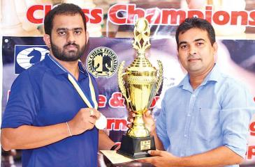 99X Technology Application Security Engineer Pranieth Chandrasekara (left) receives the trophy from Chess Federation of Sri Lanka Treasurer Irosh Jayasinghe.