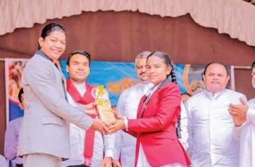 Susanthika Jayasinghe receiving a special replica from her first school Uduwaka Kanishta Vidyalaya presented by a student    in the presence of Sports Minister Namal Rajapaksa and State Minister Thenuka Vidanagamage
