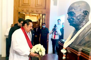 Prime Minister Mahinda Rajapaksa places a floral bouquet at the statue of  Mahatma Gandhi