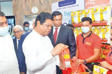Minister of Trade Bandula Gunawardena makes a purchase at the Lanka Sathosa stall using a LankaQR enabled app. Pic: Wasitha Patabendige