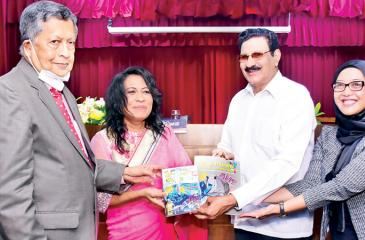Hassim Omar receiving the first copies of the books from  the Chief Guest.