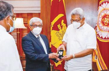 Central Bank Governor Prof. W. D. Lakshman presents the coin to President Gotabaya Rajapaksa