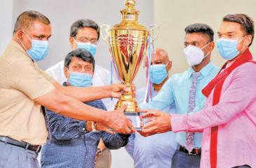 """Sports Minister Namal Rajapaksa unveiling the """"Hambantota League Football Trophy"""" along with Dr. Chanaka Wijetunga (left) Secretary of the Hambantota District Sports Foundaton. Other officials are also in the picture"""