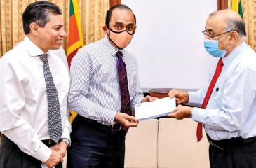 The Chairman of the People's Bank and People's Leasing, Sujeewa Rajapakse presents a cheque for Rs. 5 million to the Secretary to the President Dr. P. B. Jayasundara. Former CEO and GM of PLC, Sabry Ibrahim looks on.