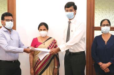 Alumni Association President Rajeev Amarasuriya exchanges the MoU with KWA Architects Partner Thilan Koththigoda. Vice Chancellor Chandrika Wijeyaratne and Alumni Head of Administration Sunethra Peiris look on.