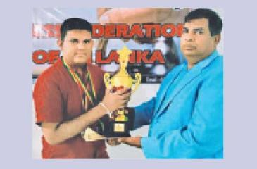 Sri Lankan Chess Grand Prix champion Ranindu Liyanage receiving the Champions trophy from the chief guest CFSL president Luxman Wijesuriya