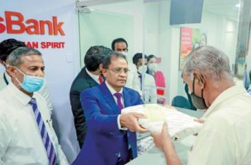 Managing Director and CEO of Cargills Bank, Senarath Bandara makes the first transaction following the opening of the branch.