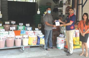 Manager, Merchant Acquiring, DFCC Bank, Chrishan Jayamanne (in the middle) presents a QR Code, POS material to a merchant at the Narahenpita Economic Centre during the promotional campaign.