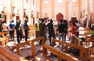 Security personnel walk through debris following the Easter Sunday  attacks in St Sebastian's Church, Negombo