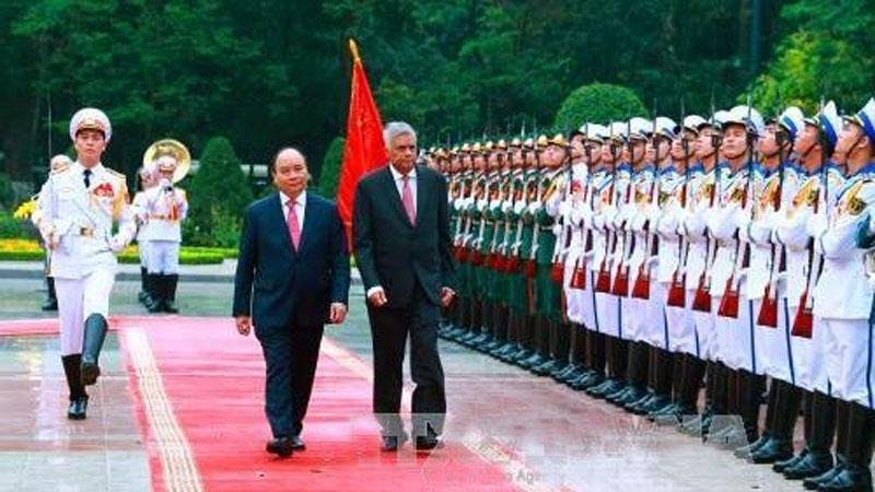 Prime Minister Ranil Wickremesinghe with his Vietnam counterpart  Nguyen Xuan Phuc inspect the guard of honour at an official welcoming ceremony for the former  in Hanoi on April 17 this year.