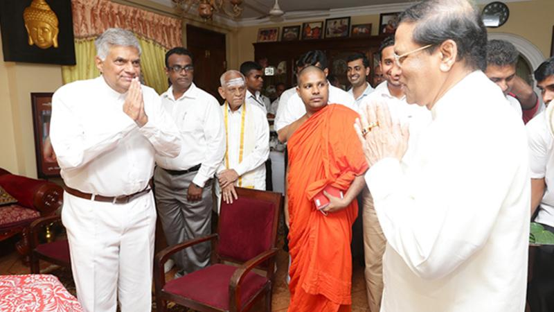 Picture issued by Prime Minister Ranil Wickremesinghe's office of him speaking with President Maithripala Sirisena Oct 13, 2016 at the Walukarama temple in Colombo. (www.economynext.com)
