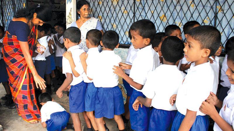 Schoolchildren pay obeisance to their class teacher on World Teacher's Day. Pic: Sulochana Gamage