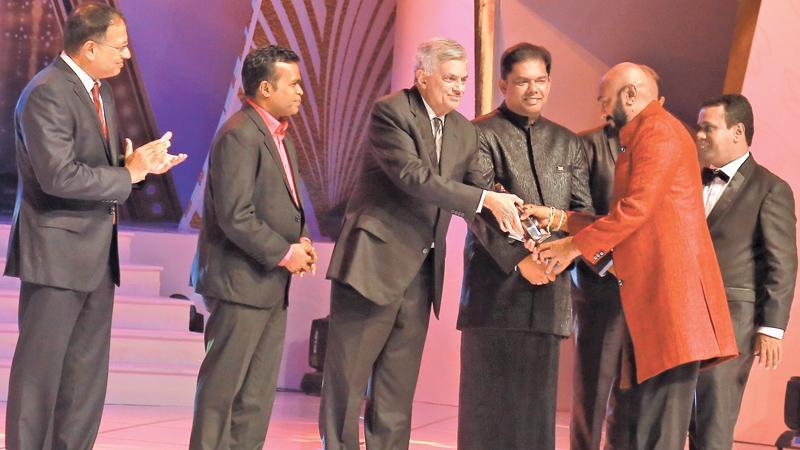 Prime Minister, Ranil Wickremesinghe presents the Best Actor's Award to Jackson Anthony while Mass Media Minister Gayantha Karunathilaka, Mass Media Deputy Minister Karu Paranawithana, ANCL Chairman Kavan Ratnayaka and Sarasaviya Weekly Editor Aruna Gunaratne look on.