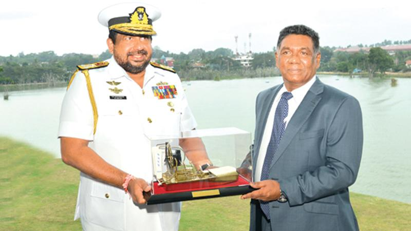 Navy Commander Vice Admiral Ravindra Wijegunaratne handing over a miniature replica of the air boat to Defence Secretary Karunasena Hettiarachchi