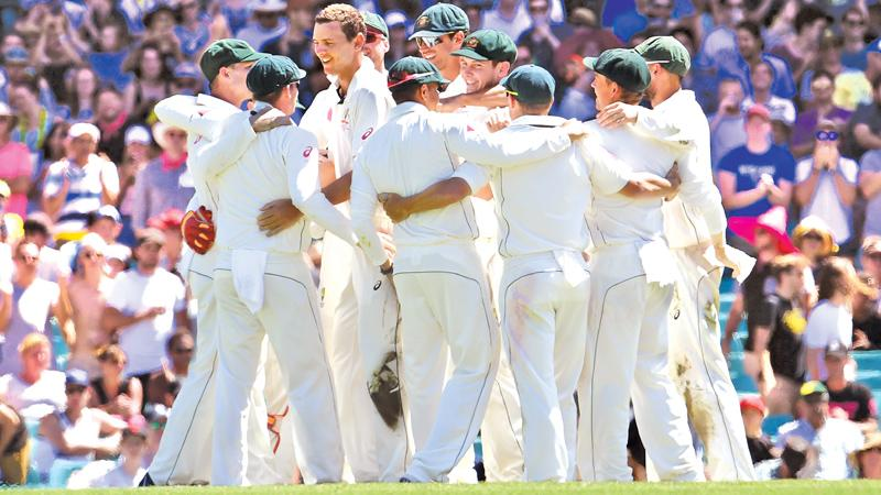 Australia's cricket team gather to celebrate after defeating Pakistan on the final day of the third cricket Test match. AFP