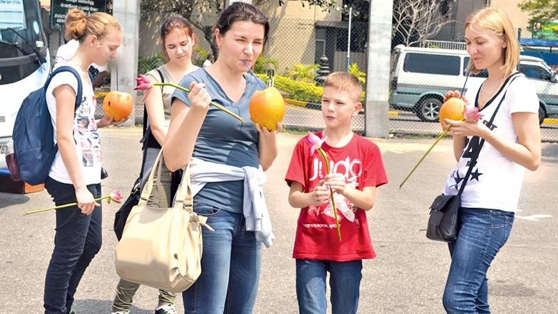 Tourists enjoy king coconuts on their arrival at BIA. Picture by Kumarasiri Prasad - File Photo