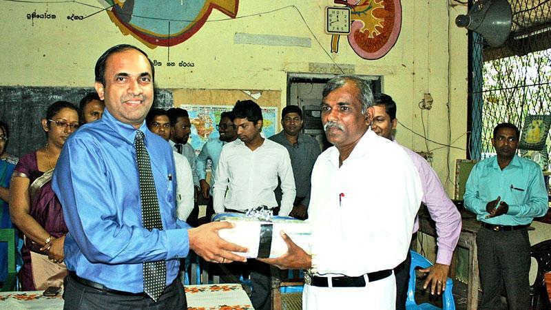 CSE CEO Rajeeva Bandaranaike hands over a set of books to the Principal of Diganegama Vidyalaya