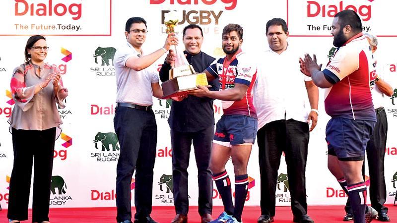 Kandy SC skipper, Roshan Weeraratne, receiving the Dialog Rugby League trophy from Sports Minister Dayasiri Jayasekera in the presence of Supun Weerasinghe, Group Chief Executive, Dialog Axiata PLC, Amali Nanayakkara, Group Chief Marketing Officer, Dialog Axiata PLC, Lasitha Gunaratne, vice president Sri Lanka Rugby and (partly hidden) Nihal Ratwatte, president,  Kandy SC.