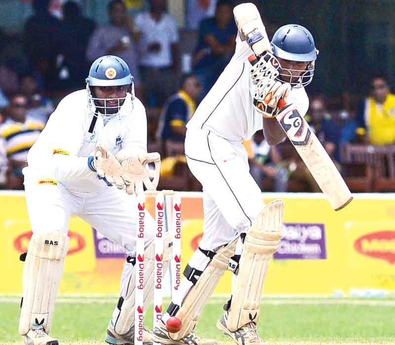 Josephian batsman Nipun Sumasinghe batting in the second innings watched by Peterite skipper and wicket-keeper Lakshina Rodrigo on the second day of the 83rd Battle of the Saints cricket match played at the P Sara Oval yesterday.  (Pic by Saman Mendis)