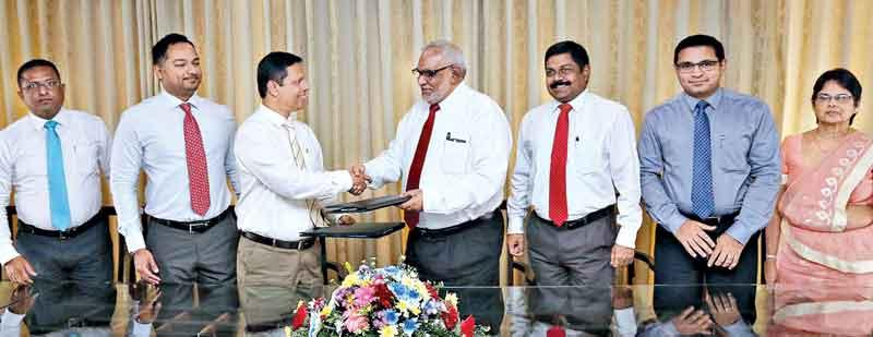 Commercial Bank Managing Director/CEO Jegan Durairatnam (fourth from right) exchanges the agreement with Tilak Dias Gunasekara, Managing Director of Sathosa Motors. Senior executives of the two institutions look on.