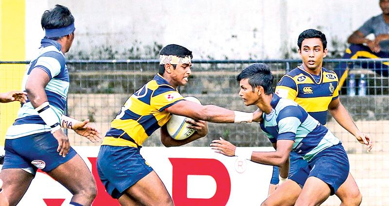 Pic. Saman Sri Wedage A Royal College player  trying to  evade a tackle  from a Wesley College player  during  their inter-school rugby  encounter at  the Royal College Sports Complex grounds at Stanley Wijesundera Mawatha yesterday.