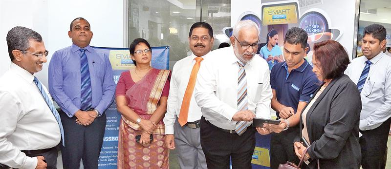 Commercial Bank Managing Director Jegan Durairatnam (fourth from left) enrols a customer through the tab based app at the Wellawatte branch. Members of the senior management of the Bank look on.