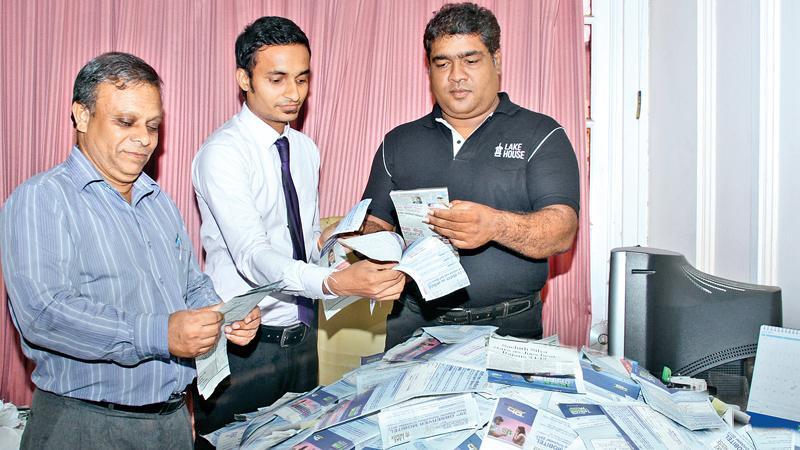Weekly reader's winning coupons. From left: Gamini Ramanayake ( Pictures Editor, ANCL), Eranda Vithanage (Manager, Treasury) and D.S.llesinghe ( Senior Manager Sales) picking the winning coupons. Picture by Saliya Rupasinghe